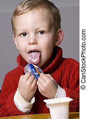Boy eating yogurt - Little boy eating yogurt or yoghurt with...