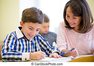 group of school kids writing test in classroom - education,...