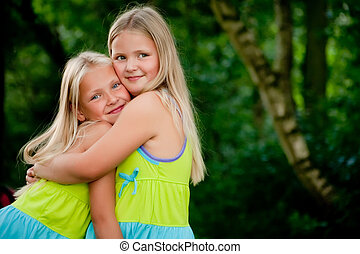 Hugging twins - Happy children having fun in the park