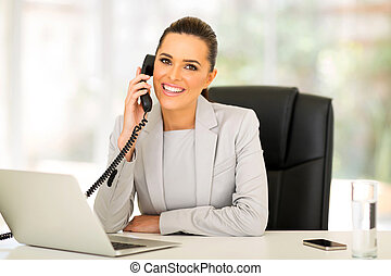 young businesswoman talking on landline phone - beautiful...