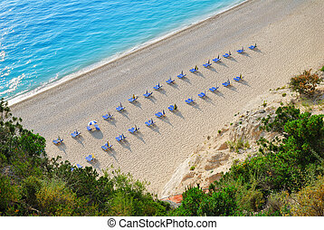 Sandy beach with empty sunbeds viewed from above