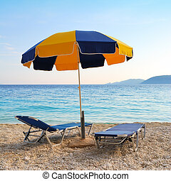 Colorful sun umbrella and two sunbeds