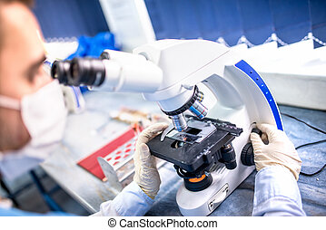 Chemist researcher working with microscope for forensic...