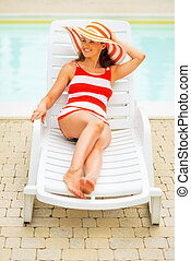 Smiling young woman laying on chaise-longue
