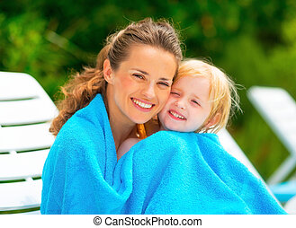 Portrait of smiling mother and baby girl wrapped in towel...