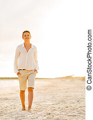 Portrait of happy young woman walking on beach at the...