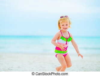 Baby girl in sunglasses playing on beach