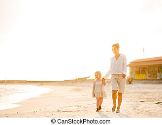 Happy mother and baby girl walking on beach at the evening