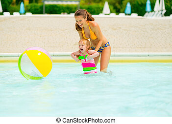 Happy mother and baby girl playing with beach ball in pool