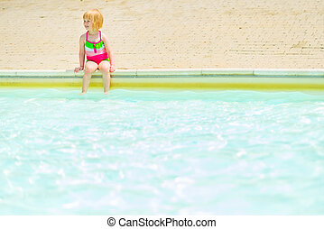 Baby girl sitting near pool