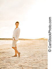 Full length portrait of young woman on beach at the evening