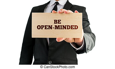 Be open-minded - Businessman holding rectangular wooden sign...