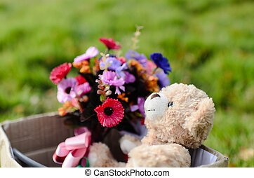 Bear and flower bouquet in brown box on green grass with...