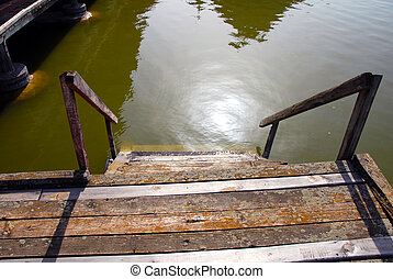 Wooden stairs into water - old shabby wooden staircase on...