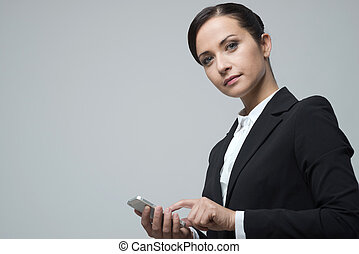 Smiling confident businesswoman using touch screen mobile...