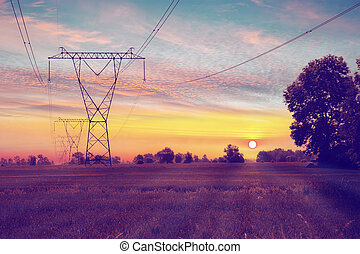 Power lines  - Electric towers on a field with sunrise.