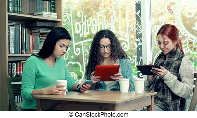 Gadget-Busy - Three girlfriends sitting in cafe with digital...