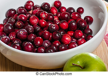 Bowl of cranberries with a green apple - A white bowl of...