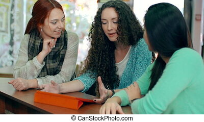 Friendly Talk - Three girls using one device and discussing...