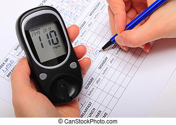 Hand of woman writing data from glucometer to medical form,...