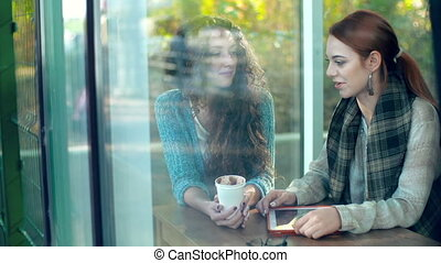 Joyful Conversation - Through the window of cafe shot of two...
