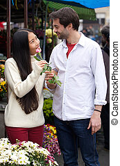 Happy young couple standing by flower shop - Portrait of a...