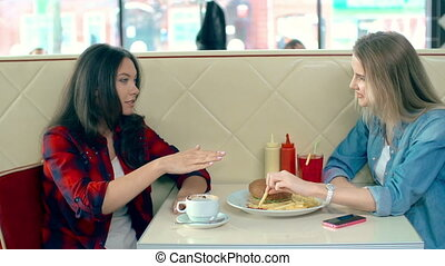 Eating Out - Two friends sharing meal in fast food...