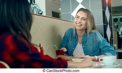 Girls at Lunch - Pretty blond girl eating French fries and...