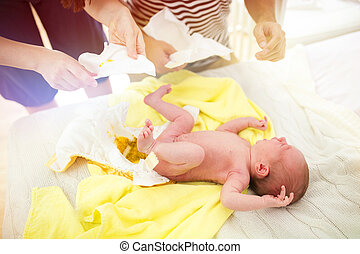 Parents changing baby nappy - Parents changing babby poop...