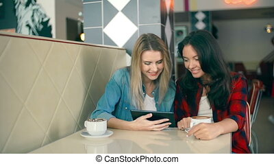 Friends in Cafe - Two girls using touch screen device