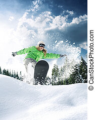 riding - view of a young girl snowboarding in winter...