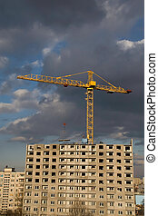 Construction site on gloomy weather - Hoisting crane lifting...