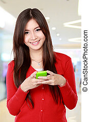 Smiling woman texting on cell phone
