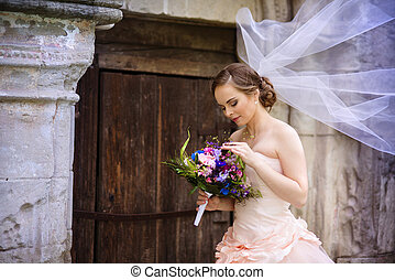 Beautiful bride in veil standing by the old stone chapel.