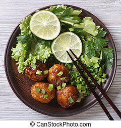 Fish balls in curry sauce with fresh herbs close up. top...