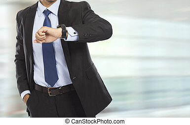 business man looking at the time on his watch - portrait of...