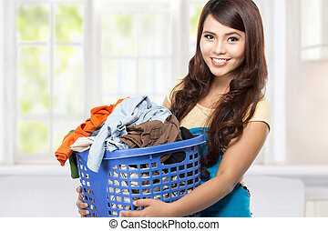 housewife with laundry - woman doing a housework holding...