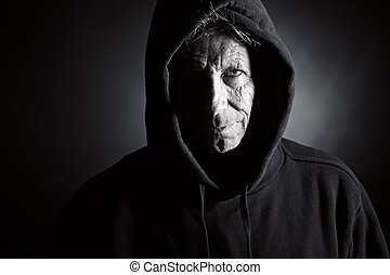 Low Key Shot of an Intimidating Senior Male in Hooded Top
