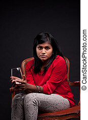 serious indian girl sitting with a glass of wine -...