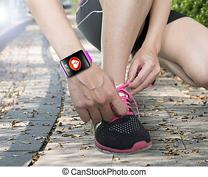 human hand tying shoelaces wearing bright pink watchband...
