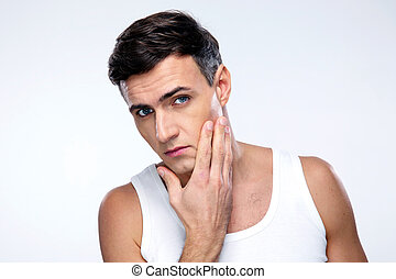 Young man after shaving over gray background