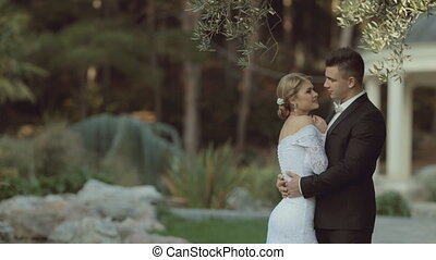 The groom in a suit hugging the bride in an elegant dress and she puts her head on his shoulder in the middle of the park