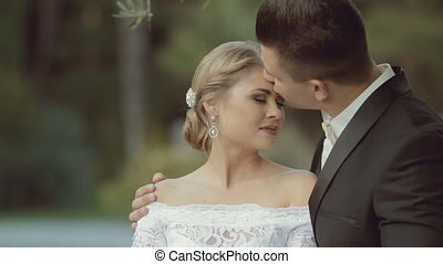 The groom gently kisses his beautiful bride, who laughs