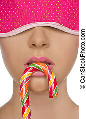 young woman with candy in his mouth and blindfold -...