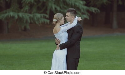 Beautiful wedding couple on green grass near the forest