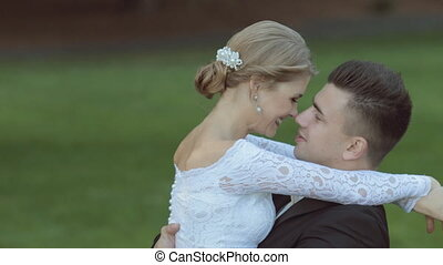 Young newlyweds enjoy each other on a background of green grass