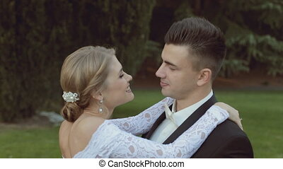 Charming bride smiling, laughing and kissing her groom, while standing on green grass
