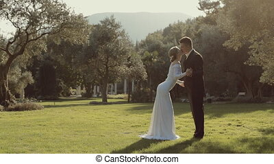 Fashionable young wedding couple kiss each other in a park