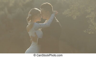 Bride in a remarkably beautiful dress with a train put her head on groom's shoulder