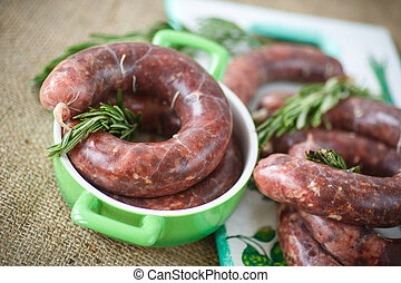 home hepatic raw sausage with rosemary on a table